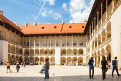 KRAKOW POLEN - JUNI 08, 2016: Grupp av turister som omkring ser på den centrala delen av den välkända Wawel kungliga slotten i Kr Arkivbilder