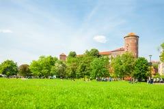 KRAKOW POLEN - JUNI 08, 2016: Massor av människor som går nära det historiska komplexet av kungliga Wawel, rockerar med väl sedda Arkivbilder