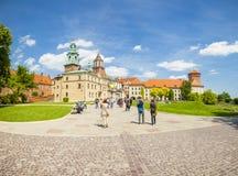 KRAKOW POLEN - JUNI 08, 2016: Turister på deras väg in mot det historiska komplexet av den Wawel den kungliga slotten och domkyrk Arkivfoto