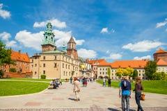 KRAKOW POLEN - JUNI 08, 2016: Turister som heading in mot det historiska komplexet av den Wawel den kungliga slotten och domkyrka Arkivbilder