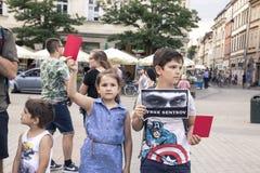 Krakow Polen, Juni 01, 2018, två barn med affischer och rött Royaltyfri Fotografi