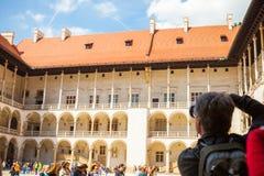 KRAKOW POLEN - MAJ 16, 2015: Fotograf som tar skott på den centrala delen av den välkända Wawel kungliga slotten i Krakow, Polen  Royaltyfria Foton
