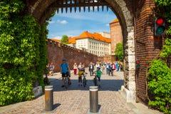 KRAKOW POLEN - MAJ 16, 2015: Turister som passerar till och med Bernardine Gate som uppslagsord till det historiska komplexet av  Arkivbilder