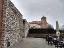 Krakow/Polen - mars 23 2018: Ett kafé på territoriet av den Wawel slotten Tornen och väggarna av slotten arkivfoton