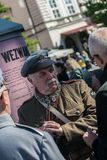 Krakow Polen - September 23, 2018: nMan iklädda polska likformig från världskrig I som rymmer en hagelgevär som talar med royaltyfri fotografi