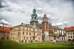 Krakow Polska, Czerwiec, - 04, 2017: Wawel katedra z kaplicami na zielonym wzgórzu Turyści przy kościół katolickim na chmurnym ni Obrazy Stock