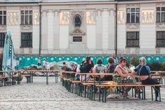 KRAKOW, POLSKA, Kwiecień 21, 2018, Wiele ludzie siedzi przy drewnianym portab Obrazy Stock