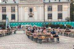KRAKOW, POLSKA, Kwiecień 21, 2018, Wiele ludzie siedzi przy drewnianym portab Obrazy Royalty Free