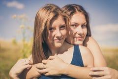 Kram för två lycklig le flickor över blå himmel Royaltyfria Bilder