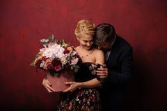 Kram för ung man hans kvinna med buketten av blommor royaltyfri foto