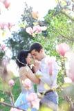 Krama för pojke för brunett europeiskt och kyssande caucasian flicka nära magnolia royaltyfria bilder