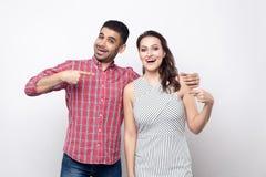 Krama för vänner Stående av den lyckliga upphetsade stiliga mannen i den röda rutiga skjortan, härlig kvinna i det vita randiga k arkivbilder
