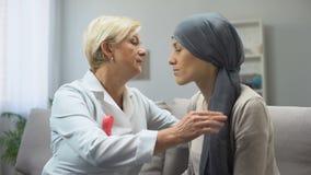 Krama och stöttande kvinna för sjuksköterska efter kemoterapi som slåss mot cancer lager videofilmer
