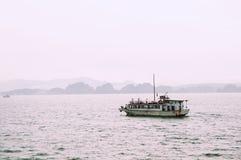 Krambootssegeln über regnerischer halong Bucht Vietnam mit Land im Hintergrund lizenzfreie stockfotos