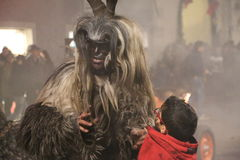 Krampus with a small child. Brixen/Bressanone, South Tyrol, Italy - December 05, 2013: A traditional parade of the Krampus, beast-like creatures march through Stock Photography