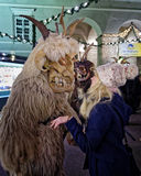 Krampuslauf in Salzburg. SALZBURG, AUSTRIA - DECEMBER 21: A wooden mask wearing person bewitches a visitor of the Christmas Market during the Christmas Devil Run Royalty Free Stock Images