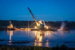 Kran auf dem Schiff produziert Sand auf dem Fluss stockfotos