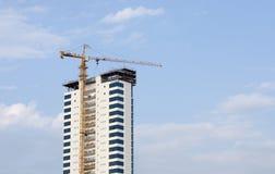 Kran bei der Arbeit über ein hohes Gebäude Stockfotografie