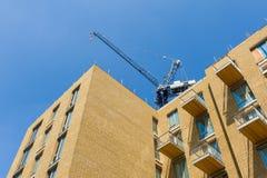 Kran über dem Gebäude Stockbild