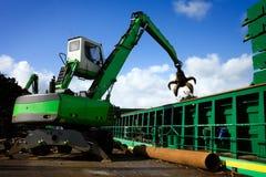 Kran, der eine Lieferung mit der Wiederverwertung des Stahls belädt Stockbilder