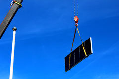 Kran, der einen großen Sonnenkollektor anhebt Lizenzfreies Stockbild