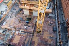 Kran, der im Bau durch Boden von Highrise steigt Stockbilder