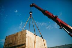 Kran hebt schweren Behälter auf einem LKW an lizenzfreies stockfoto