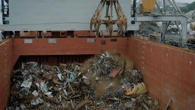 Kran med magneten i process av att dumpa avfall i behållare arkivfilmer