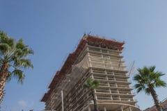 Kran mot himmel som bygger ett nytt flerbostadshus nytt m?ng--v?ning hus arkivbild
