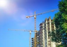 Kran och arbetare på konstruktion av residental byggnad Royaltyfria Bilder
