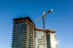 Kran och byggandekonstruktion med klar blå himmel royaltyfri foto