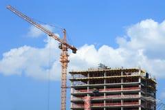 Kran och byggnad under konstruktion mot blå himmel Arkivbild