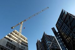 Kran och byggnader mot blå himmel Royaltyfri Foto