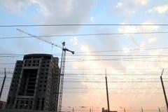 Kran- och byggnadskonstruktionsplats mot blåttskyen Arkivfoton