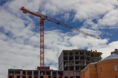 Kran- och byggnadskonstruktionsplats mot blåttskyen Arkivfoto