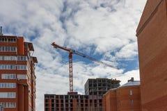 Kran- och byggnadskonstruktionsplats mot blåttskyen Arkivbild