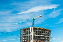 Kran och höghus under byggnationer mot blå himmel för sol Royaltyfri Bild