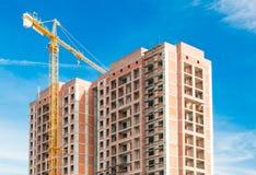 Kran och höghus under byggnationer mot blå himmel för sol Royaltyfri Fotografi