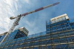 Kran och material till byggnadsställning på en nybygge Arkivbild
