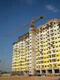 Kran och oavslutad byggnad arkivbild
