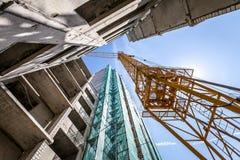 Kran på konstruktionen av byggnaden Arkivfoto