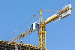 Kran på konstruktionsplats över blå himmel Royaltyfria Bilder