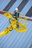 Kran und Arbeitnehmerin auf Baustelle Stockbilder