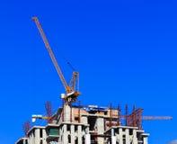 Kran und Arbeitskräfte an der Baustelle gegen blauen Himmel. Stockfoto