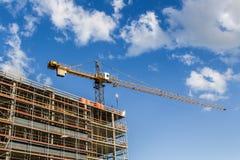 Kran- und Baugebäude Goldtasten in den Fingern mit Häusern Stockfotos