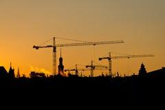 Kran- und Gebäudeschattenbilder über Sonne bei Sonnenaufgang Stockfotos