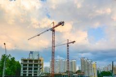 Kranar är på konstruktionsplatsen av bostads- byggnader Royaltyfri Bild