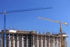 kranar för byggnadskonstruktion över lokal Arkivfoto