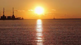 Kranar i havsporten p? solnedg?ngen, en hamn n?ra hamnstaden, en h?rlig seascape, en stor hamnstad p? solnedg?ngen lager videofilmer