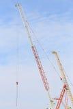 Kranar i konstruktionsplats med blå himmel och molnet Arkivfoto